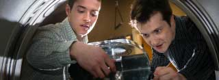 Two young men lift a glass lid on a research project.