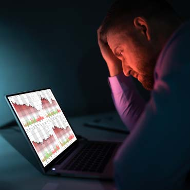 Person looking frustrated gazing at charts on a laptop computer