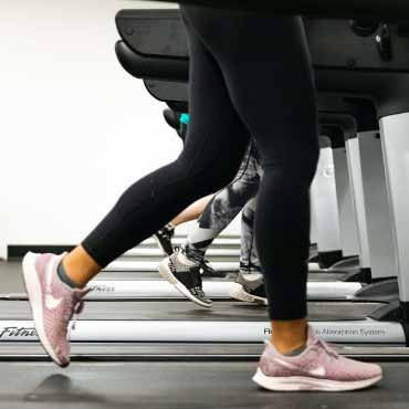 Person with pink sneakers walking on treadmill