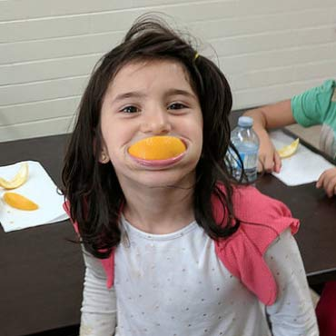 A girl with a slice of orange in her mouth