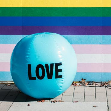 "A giant baby-blue beach ball with the word ""Love"" in front of a colourful striped wall"