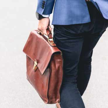 A person carrying a battered leather briefcase