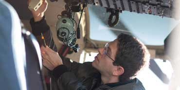 Person examining something technical in a plane's cockpit